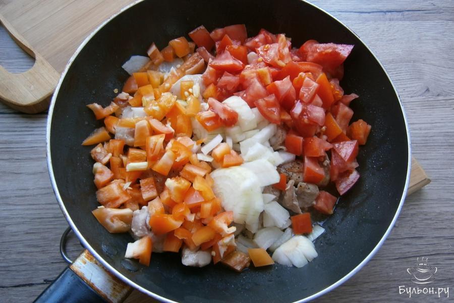 Затем, к мясу добавить порезанные кубиками: лук, помидоры и болгарский перец.