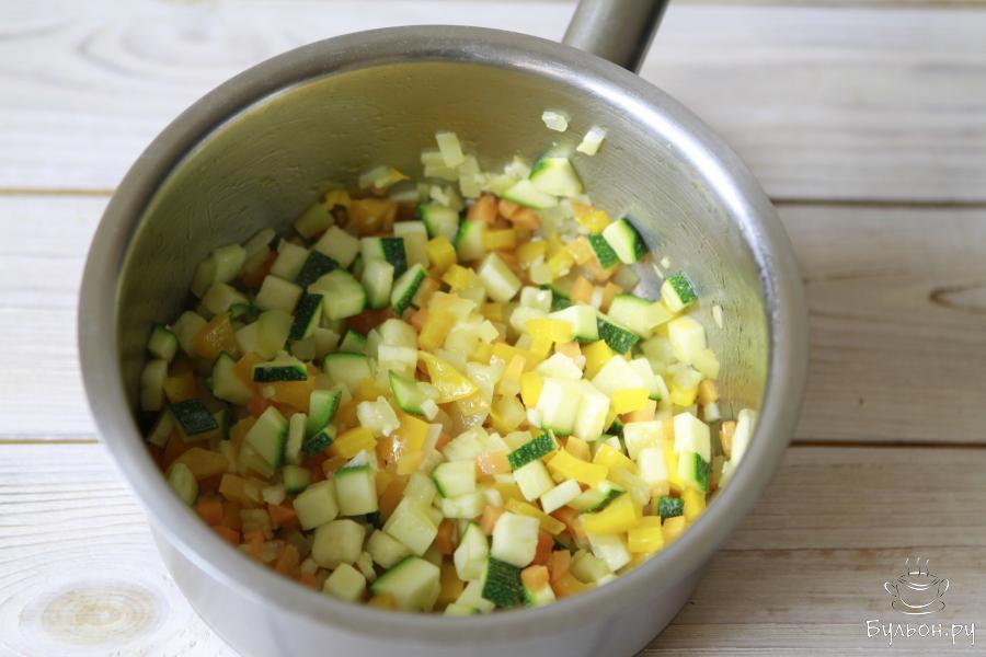 На оливковом масле припустить (буквально 5-6 минут) овощи в следующем порядке: лук, морковь, картофель, чеснок, болгарский перец и цуккини.