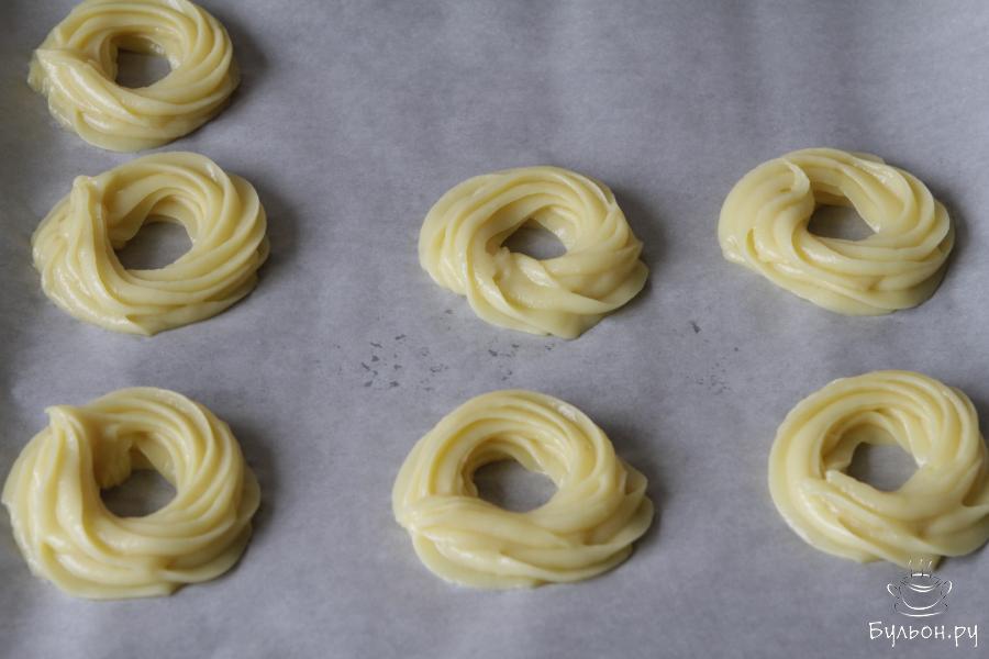 Тесто переложить в кондитерский мешок и отсадить кольца. Из этого количества получается 7-8 колец диаметром 8-9 см.