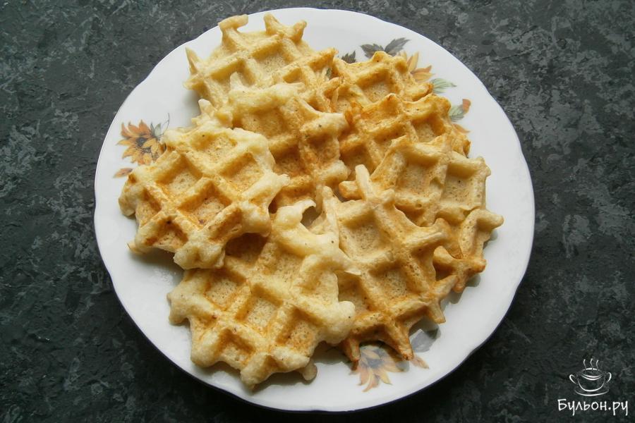 Каждый раз, после выпечки очередной партии вафель, электровафельницу нужно смазывать растительным маслом. Сложить вафли на тарелку.