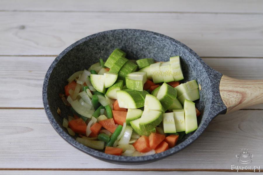 Далее к овощам добавить кабачок кубиками и стручковую фасоль. Обжарить на среднем огне не более 3-4 минут.