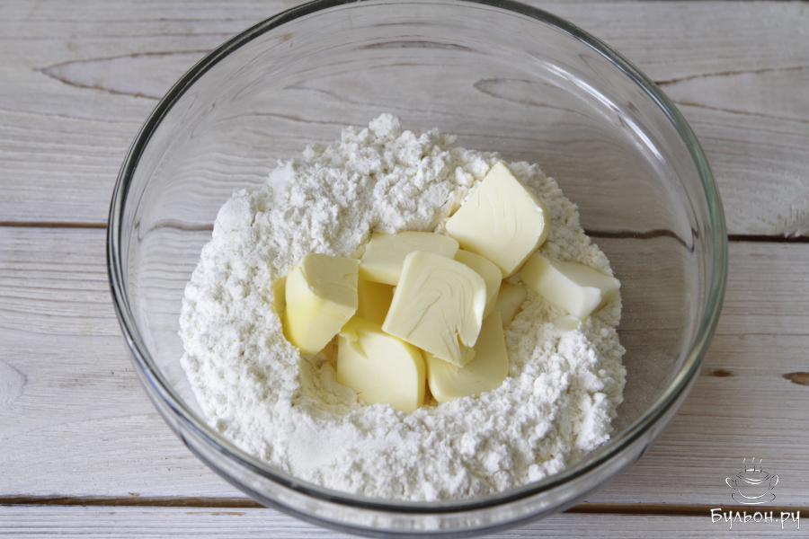 Муку просеять, добавить 1/2 ч. л. соли. Порубить охлажденное сливочное масло.