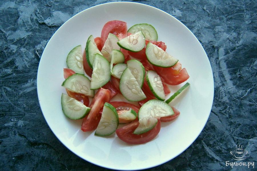 На плоскую тарелку порезать спелые, но тугие помидоры дольками, добавить порезанный тонкими полукружками свежий огурец.