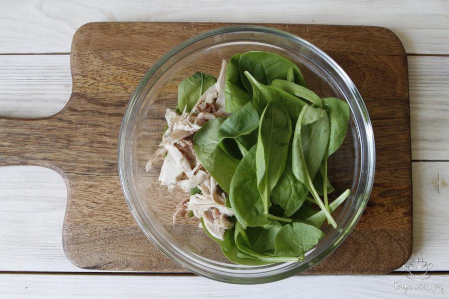 Переложить в чашу салатника листья шпината и кусочки курицы.
