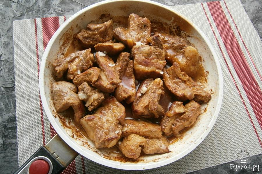 Затем, огонь уменьшить, влить бульон, лучше - овощной или простую воду, накрыть сковороду крышкой и готовить ребра минут 20. В самом конце, когда жидкость полностью испарится, добавить к мясу мелко порезанный чеснок.