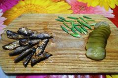 Как приготовить: чесночные гренки со шпротами. Зеленый лук нарезать перьями, соленые огурцы кружочками. У шпрот отрезать хвостики.